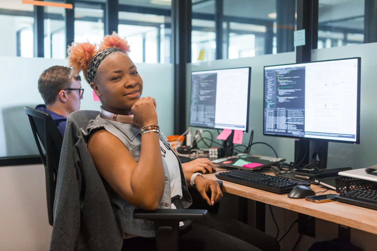 Woman sitting in front of a computer looking back towards the camera