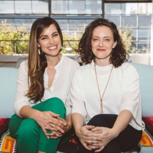 Two professional women sitting on a couch with their legs crossed and hands in front of their knees
